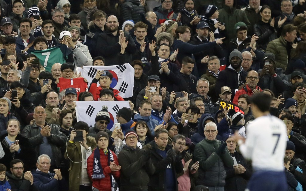 Tottenham fans hold South Korea flags during the English Premier League soccer match between Tottenham Hotspur and Bournemouth at Wembley stadium in L...