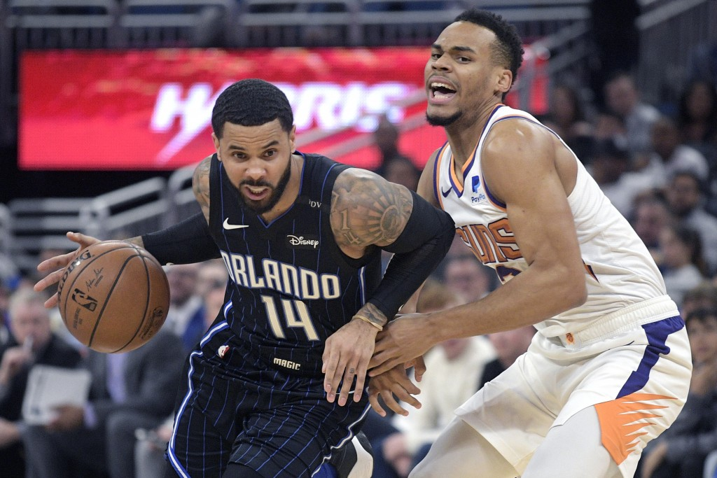 Orlando Magic guard D.J. Augustin (14) drives to the basket in front of Phoenix Suns guard Elie Okobo, right, during the first half of an NBA basketba...
