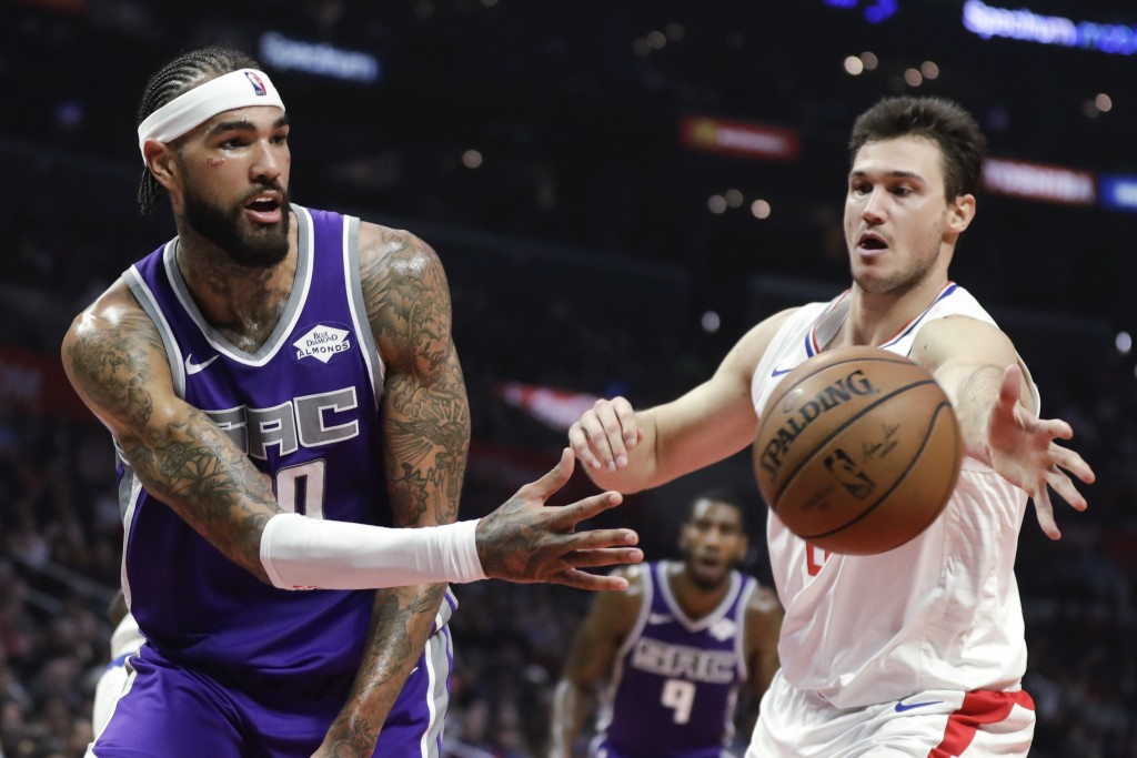 Sacramento Kings center Willie Cauley-Stein, left, passes the ball past Los Angeles Clippers forward Danilo Gallinari during the first half of an NBA ...