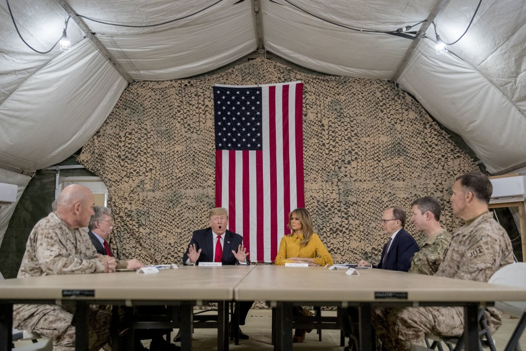 President Donald Trump, accompanied by National Security Adviser John Bolton, third from left, first lady Melania Trump, fourth from right, US Ambassa