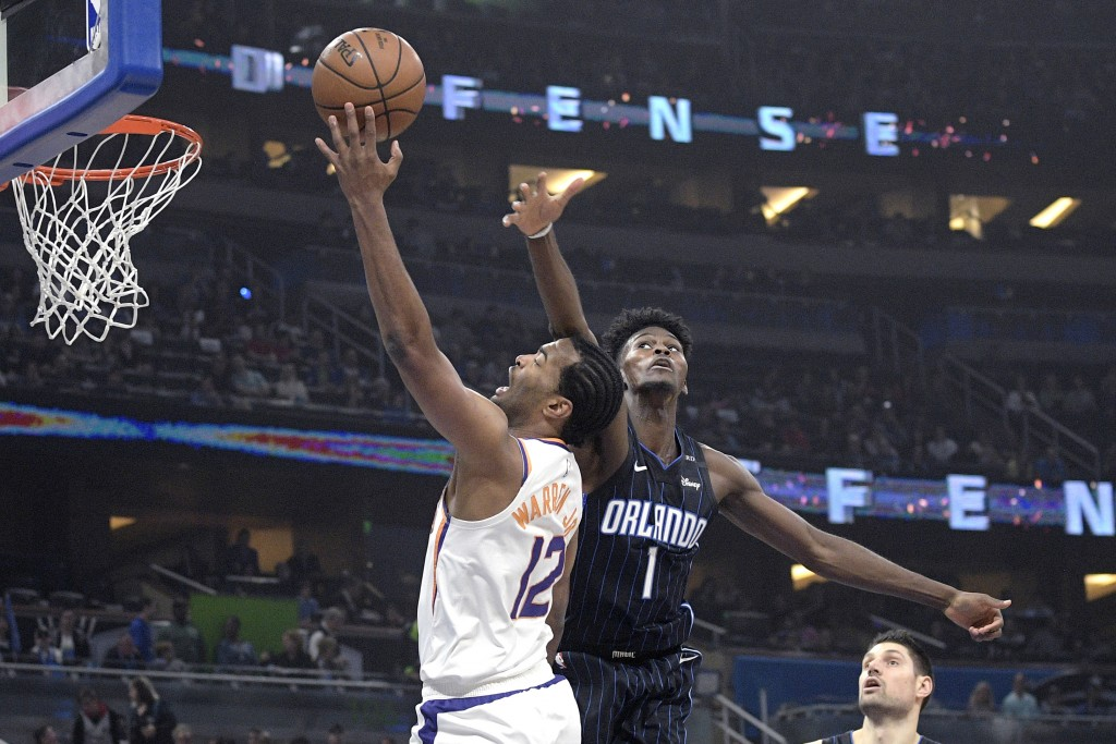 Phoenix Suns forward T.J. Warren (12) is fouled by Orlando Magic forward Jonathan Isaac (1) while going up for a shot during the first half of an NBA ...