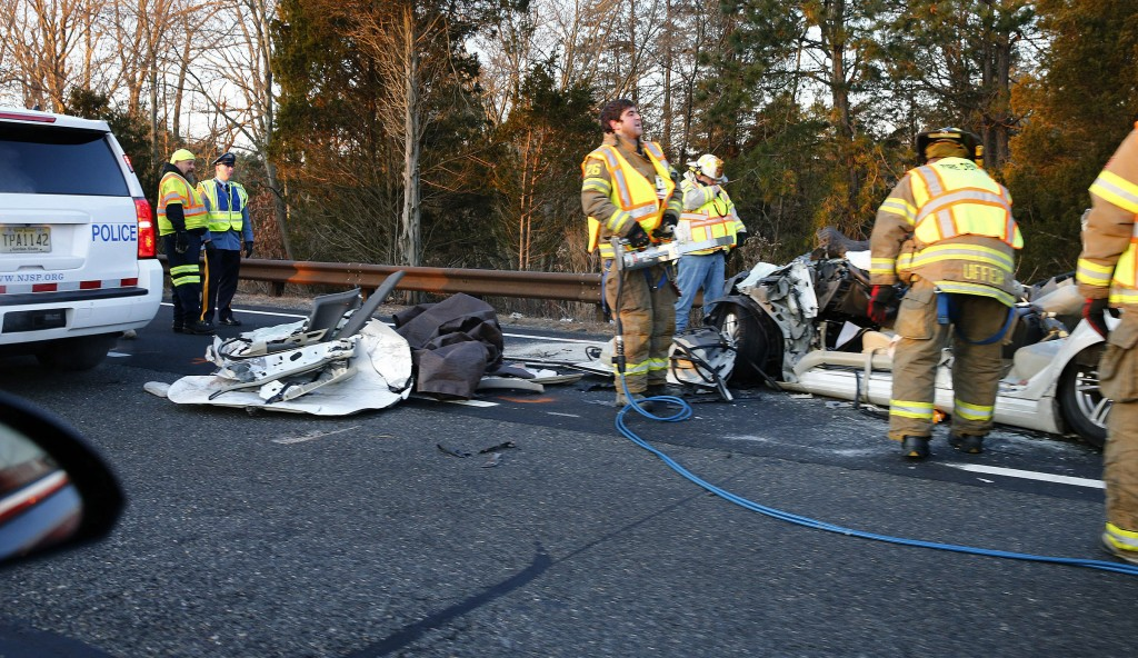 Toms River firefighters work at the scene of a car that crashed into a tanker truck in Toms River, N.J., Wednesday, Dec. 26, 2018. New Jersey state po...