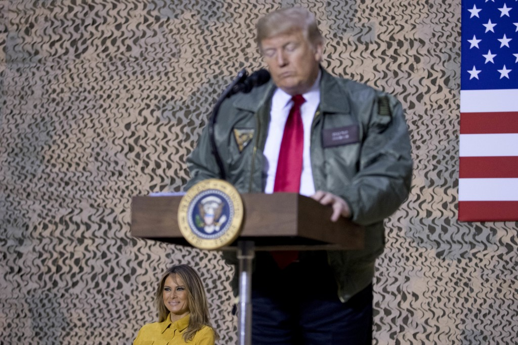 First lady Melania Trump, left, is seated on stage as President Donald Trump pauses as he speaks at a hanger rally at Al Asad Air Base, Iraq, Wednesda...