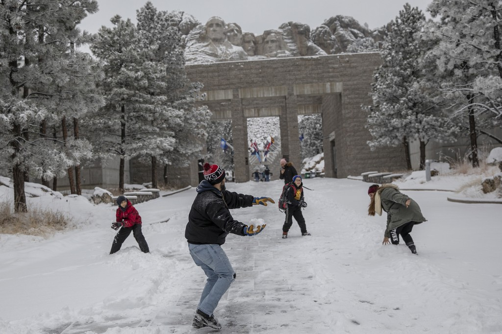 Nestor Marquez prepares to throw a snowball during a snowball fight with his children, from right, Jocelynn, 15, and Jon, 11, and family friend Anthon...