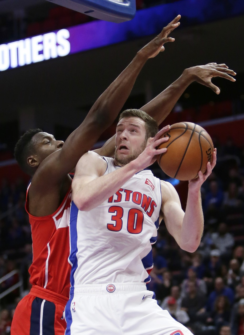 Detroit Pistons forward Jon Leuer (30) goes to the basket against Washington Wizards center Ian Mahinmi, left, during the first half of an NBA basketb