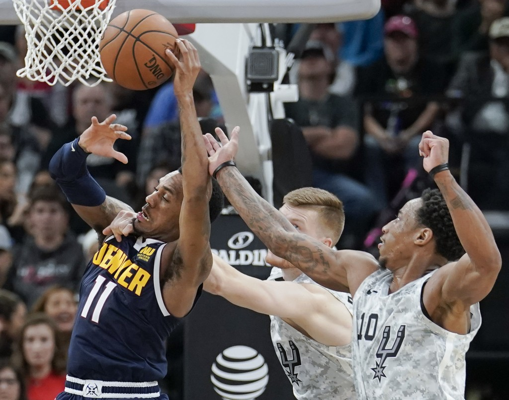 Denver Nuggets' Monte Morris, left, attempts to shoot against San Antonio Spurs' DeMar DeRozan, right, and Davis Bertans during the second half of an ...