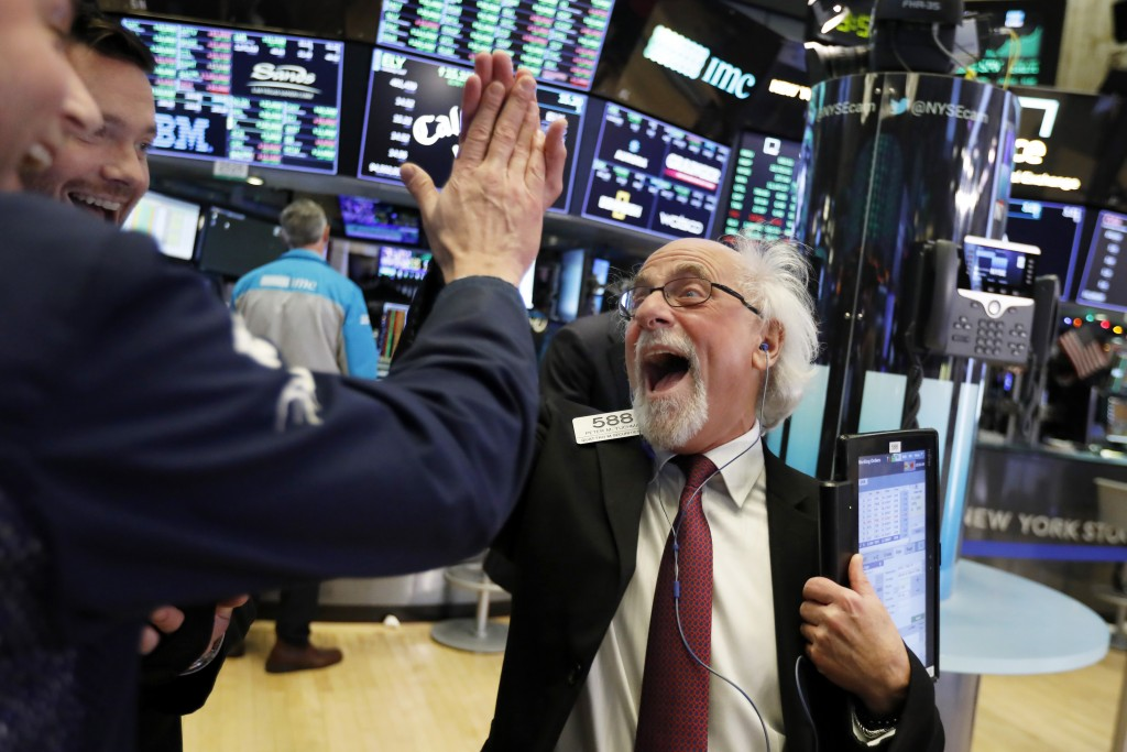 Traders Peter Tuchman, right, slaps a high five before the closing bell on the floor of the New York Stock Exchange, Wednesday, Dec. 26, 2018. The Dow...