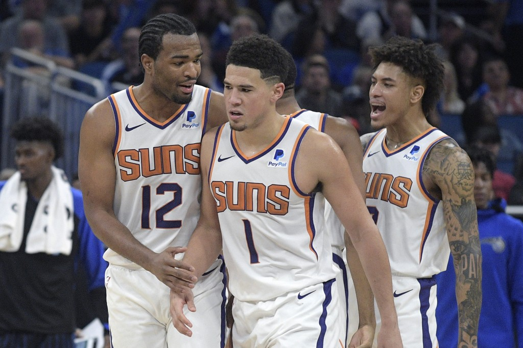 Phoenix Suns guard Devin Booker (1) is congratulated by forward T.J. Warren (12) and forward Kelly Oubre Jr., right, after making a shot during the se...