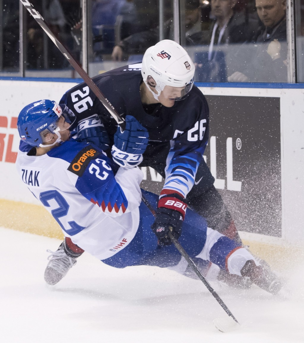 CORRECTS CITY TO VICTORIA, INSTEAD OF VANCOUVER - United States' Mikey Anderson, right, fights for control for the puck with Slovakia's Adam Ziak duri...