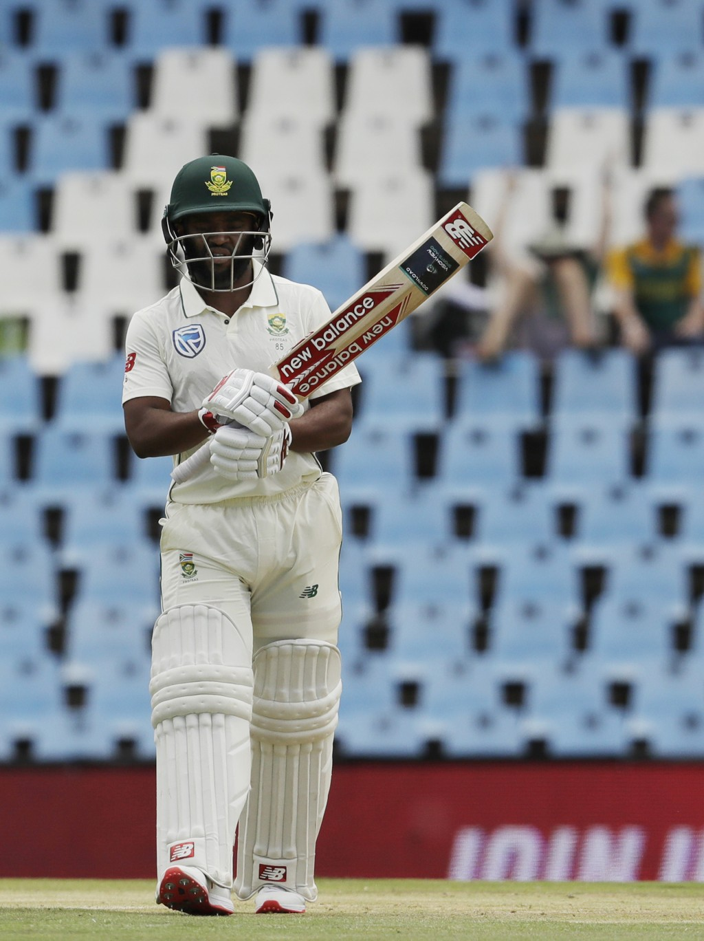 South Africa's batsman Temba Bavuma raises his bat after reaching half-century on day two of the first cricket test match between South Africa and Pak...