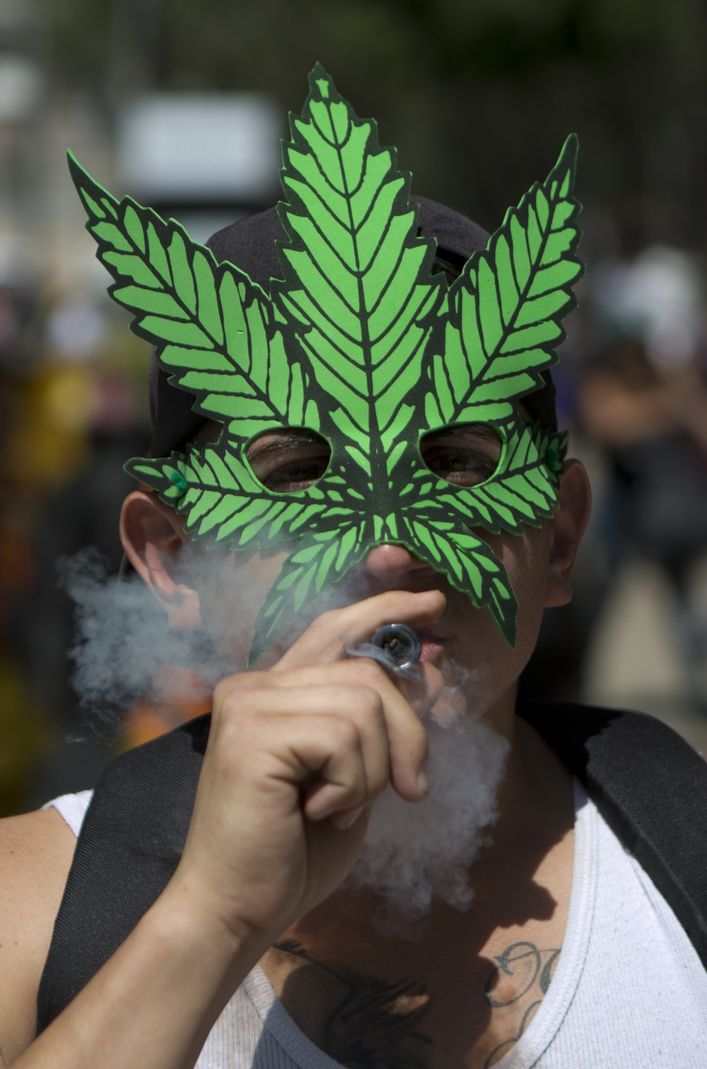 FILE - In this April 20, 2018, file photo, a young man smokes marijuana to celebrate the International Day for Cannabis in Mexico City. California bec...
