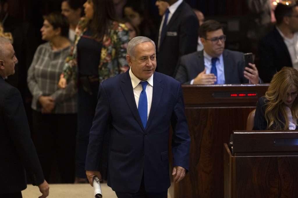 Israeli Prime Minister Benjamin Netanyahu walks in during a session at the Knesset, Israel's parliament in Jerusalem, Wednesday, Dec. 26, 2018. As sna