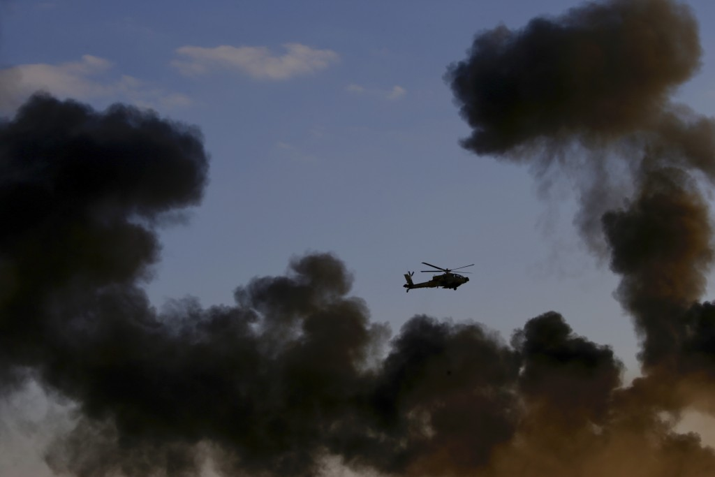 An Israeli Air Force Apache attack helicopter flies during a graduation ceremony for new pilots in the Hatzerim air force base near the city of Beersh