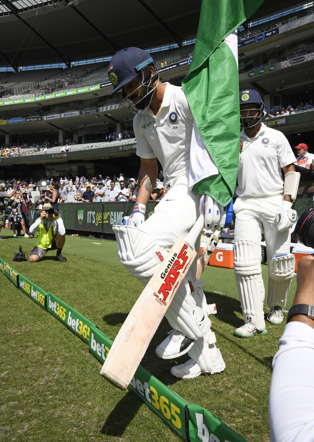 India's India's Virat Kohli, left, and Cheteshwar Pujara right enter the field before play on day two of the third cricket test between India and Aust...