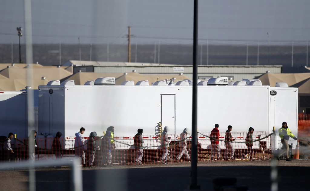 FILE - In this Dec. 13, 2018 file photo migrant teens walk in a line through the Tornillo detention camp in Tornillo, Texas. The Trump administration ...