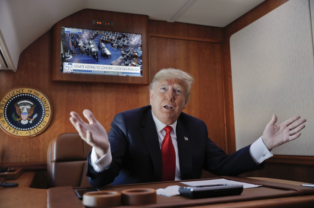 FILE - In this Oct. 6, 2018, file photo, President Donald Trump, on board Air Force One, gesture while watching a live television broadcast of the Sen...