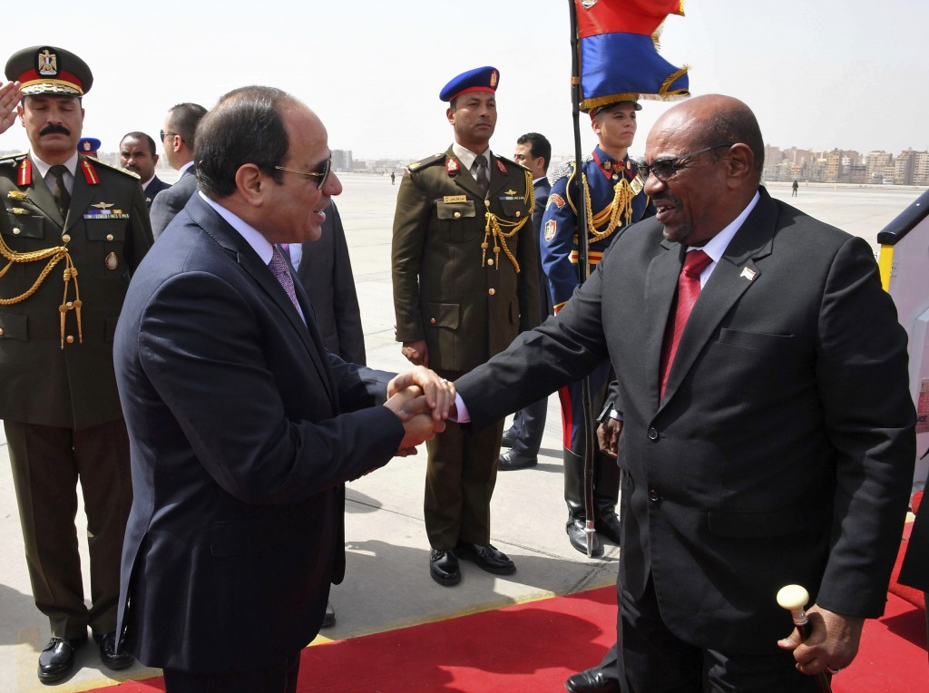FILE - In this March 19, 2018 file photo, Egyptian President Abdel-Fattah el-Sissi, left, shakes hands with Sudan's President Omar Bashir at Cairo Air...