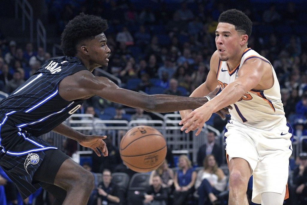 Phoenix Suns guard Devin Booker (1), right, passes the ball in front of Orlando Magic forward Jonathan Isaac (1) during the first half of an NBA baske...
