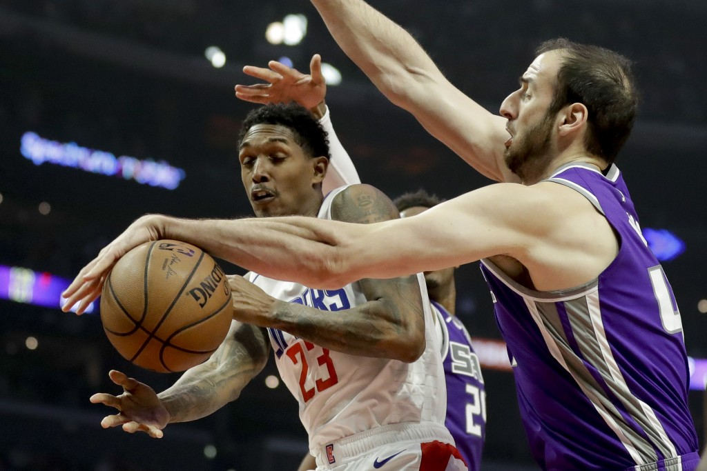 Sacramento Kings center Kosta Koufos, right, and blocks a shot by Los Angeles Clippers guard Lou Williams during the first half of an NBA basketball g...