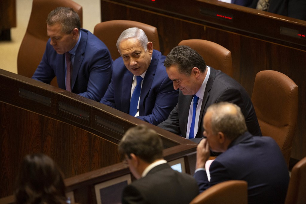 Israeli Prime Minister Benjamin Netanyahu, center, votes with Israeli Public Security Minister Gilad Erdan left, and Israeli Minister of Transportatio...