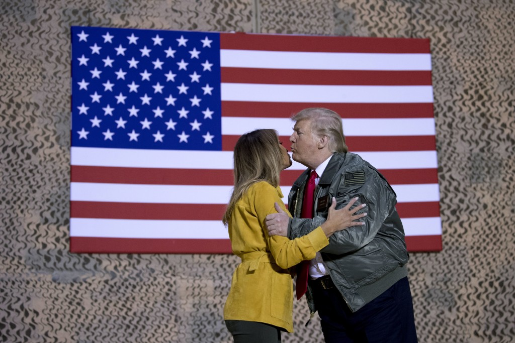 President Donald Trump kisses first lady Melania Trump during a hanger rally at Al Asad Air Base, Iraq, Wednesday, Dec. 26, 2018. President Donald Tru...