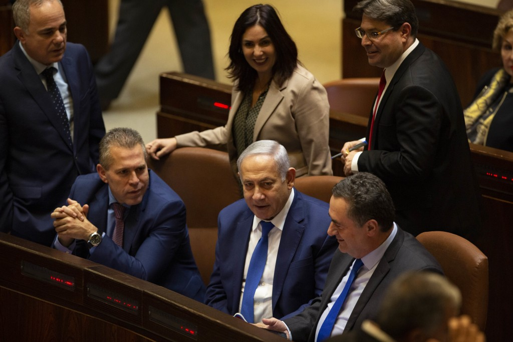Israeli Prime Minister Benjamin Netanyahu, center, speaks with Israeli Minister of Transportation Yisrael Katz right, Israeli sports and culture minis...