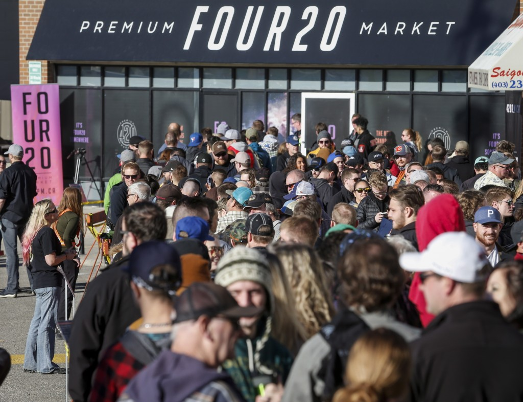 FILE - In this Oct. 17, 2018, file photo, people line-up to purchase legal cannabis in Calgary, Alberta. California became America's largest legal mar...