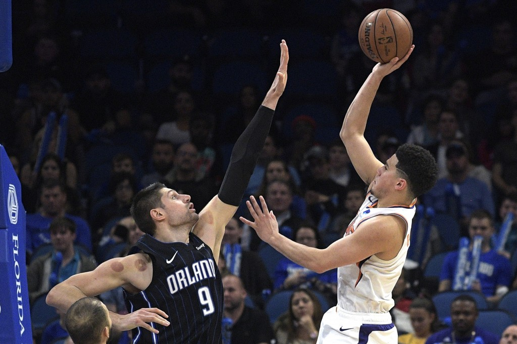Phoenix Suns guard Devin Booker, right, goes up for a shot in front of Orlando Magic center Nikola Vucevic (9) during overtime of an NBA basketball ga...