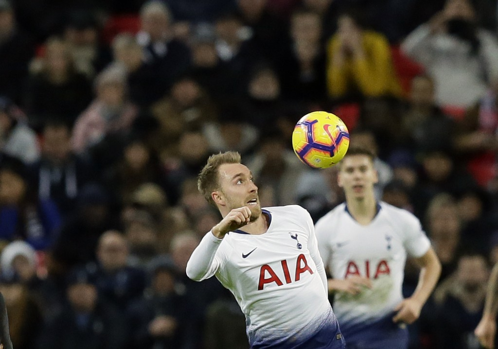 Tottenham's Christian Eriksen, center, jumps for the ball during the English Premier League soccer match between Tottenham Hotspur and Bournemouth at