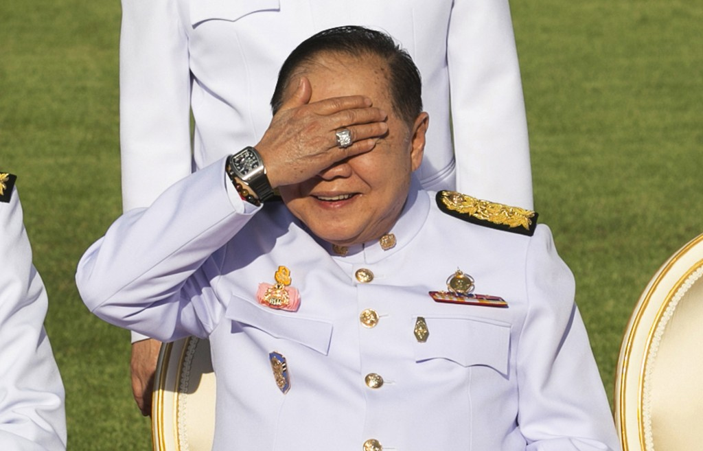 FILE - In this Dec. 4, 2017, file photo, Thailand's Deputy Prime Minister Prawit Wongsuwan raises his hand to shade his eyes from the sun while wearin...