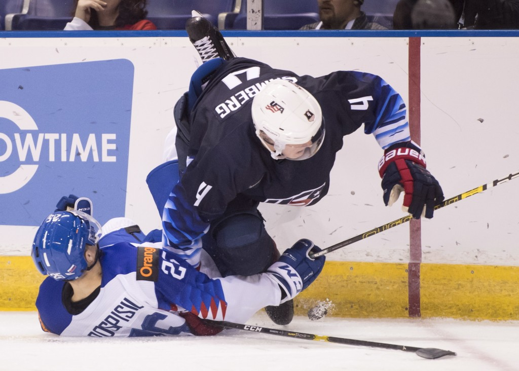 CORRECTS CITY TO VICTORIA, INSTEAD OF VANCOUVER - United States' Dylan Samberg fights for control of the puck with Slovakia's Martin Pospisil, left, d