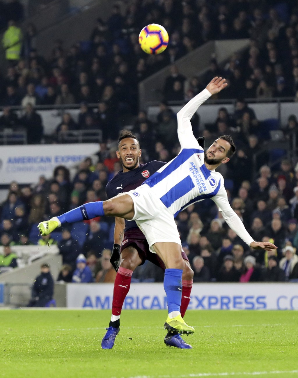 Arsenal's Pierre-Emerick Aubameyang, rear, and Brighton & Hove Albion's Martin Montoya battle for the ball during the English Premier League soccer ma...