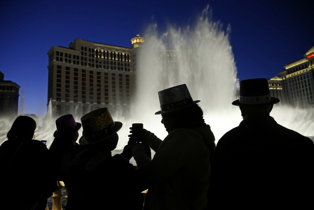 FILE - In this Dec. 31, 2015, file photo, people watch the fountains at the Bellagio while wearing paper hats to celebrate New Years Eve in Las Vegas....