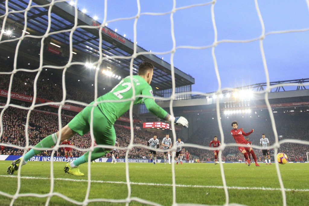 Liverpool'sMohamed Salah, right, scores on a penalty kick during the English Premier League soccer match between Liverpool and Newcastle at Anfield St...