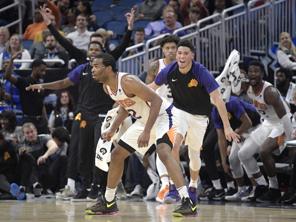Phoenix Suns forward T.J. Warren, front, strikes a pose, as his teammates celebrate off the bench after his 3-pointer as time ran out in the first qua...