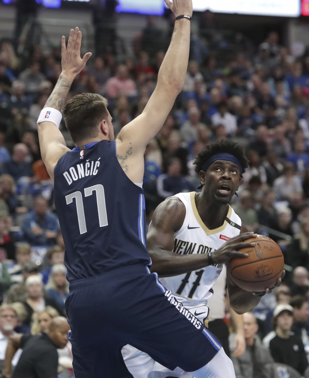 New Orleans Pelicans guard Jrue Holiday (11) looks to shoot against Dallas Mavericks forward Luka Doncic (77) during the first half of an NBA basketba...