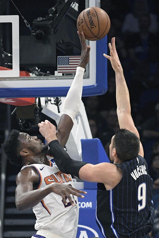 Phoenix Suns center Deandre Ayton, left, blocks a shot by Orlando Magic center Nikola Vucevic (9) during the first half of an NBA basketball game Wedn...