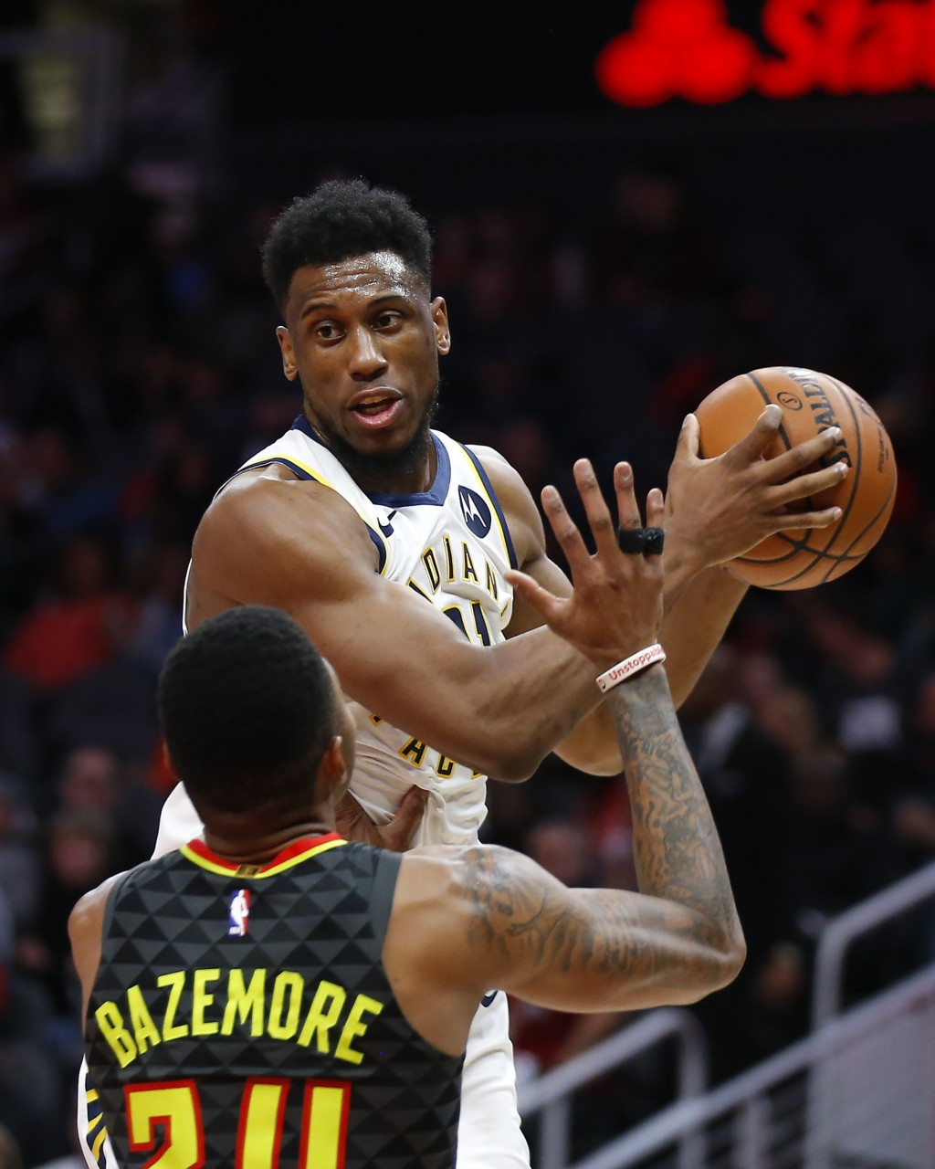 Indiana Pacers forward Thaddeus Young (21) is defended by Atlanta Hawks guard Kent Bazemore (24) during the second half of an NBA basketball game Wedn...