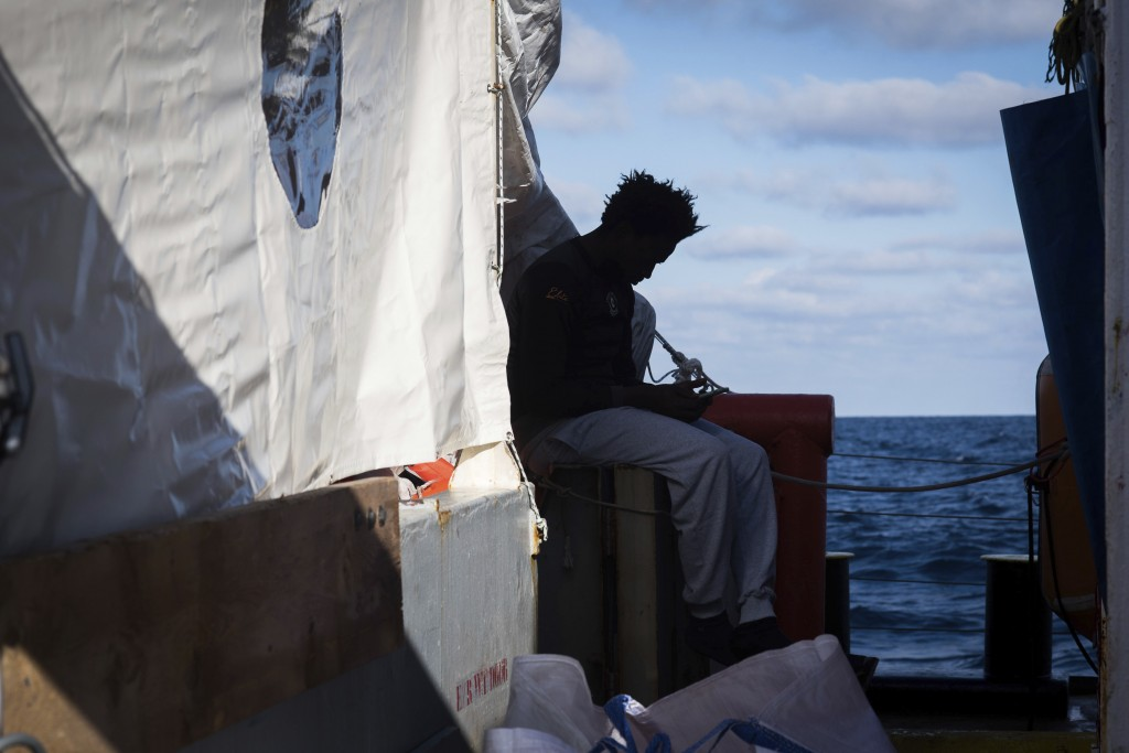 In this Monday, Dec. 24, 2018 photo and provided by Sea Watch, a migrants sits aboard the rescue ship Sea-Watch 3. Over 30 migrants saved in the centr...