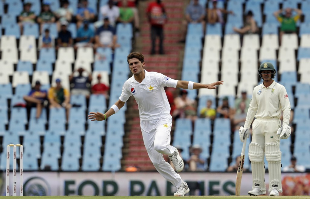 Pakistan's bowler Shaheen Afridi, left, celebrates a wicket as South Africa's batsman Quinton de Kock watches on during day two of the first cricket t...