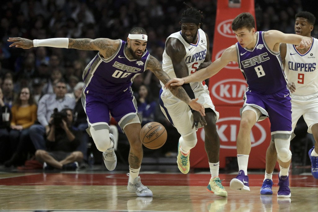 Sacramento Kings center Willie Cauley-Stein, left, and guard Bogdan Bogdanovic, right, take the ball away from Los Angeles Clippers forward Montrezl H...