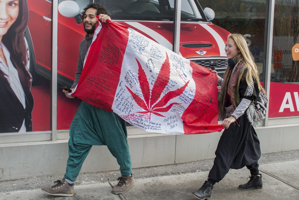 FILE - In this Oct. 17, 2018, file photo, people hold up a Canadian flag with a marijuana logo on it outside a government cannabis store in Montreal. ...