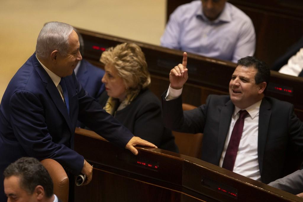 Israeli Prime Minister Benjamin Netanyahu speaks with Israeli Knesset member Ayman Odeh during a session in Jerusalem, Israel, Wednesday, Dec. 26, 201...