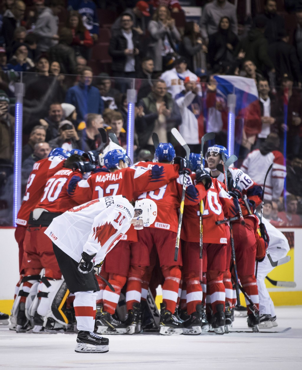 Switzerland's Yannick Bruschweiler (10) skates past as Czech Republic players celebrate their overtime win in a world junior men's hockey championship