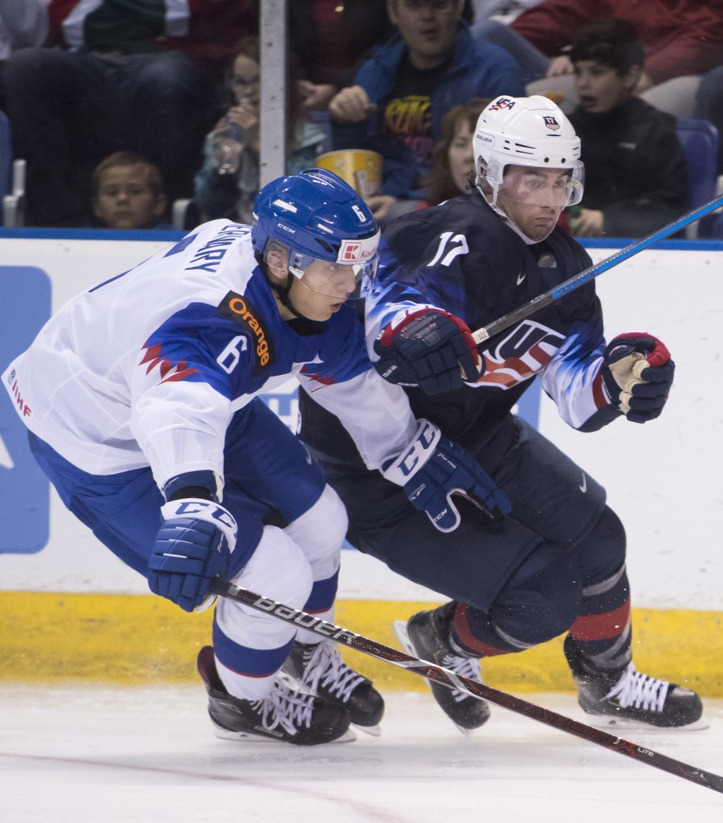 CORRECTS CITY TO VICTORIA, INSTEAD OF VANCOUVER - United States' Evan Barratt, right, fights for control of the puck with Slovakia's Martin Fehervary
