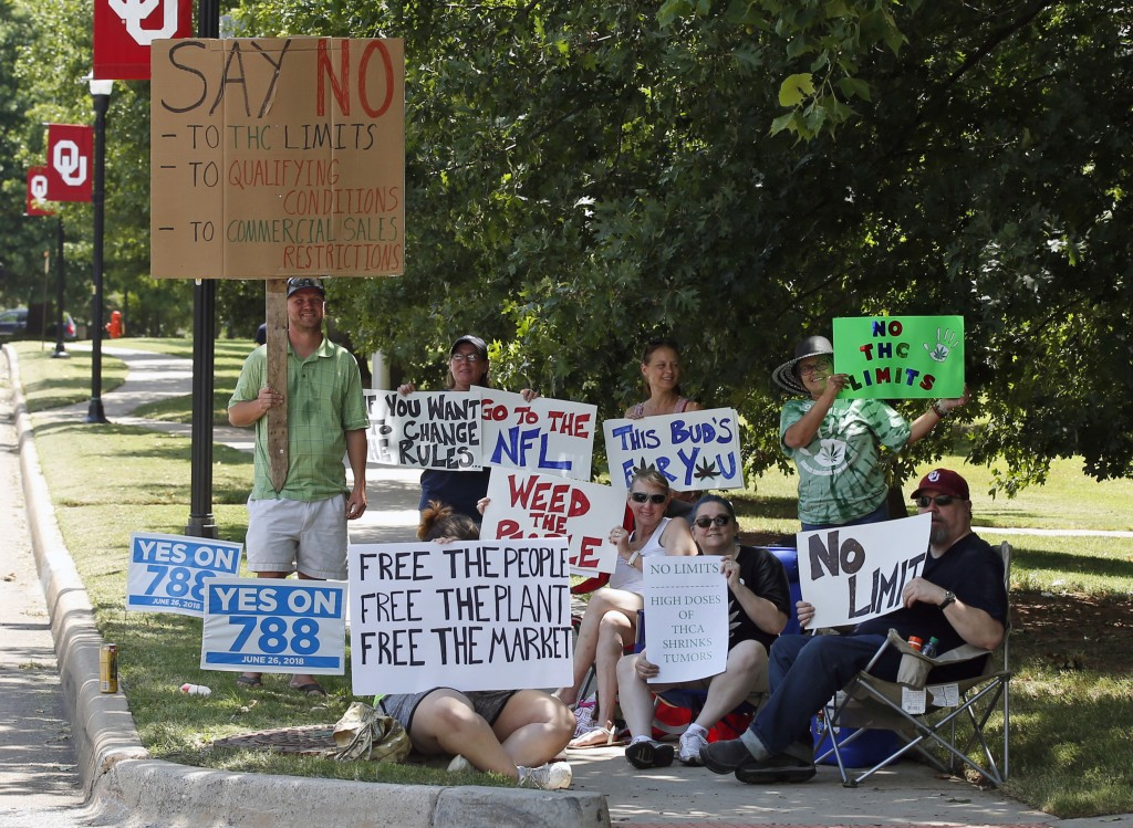 FILE - In this July 10, 2018, file photo medical marijuana supporters hold signs outside of an Oklahoma Board of Health meeting in an overflow room in...