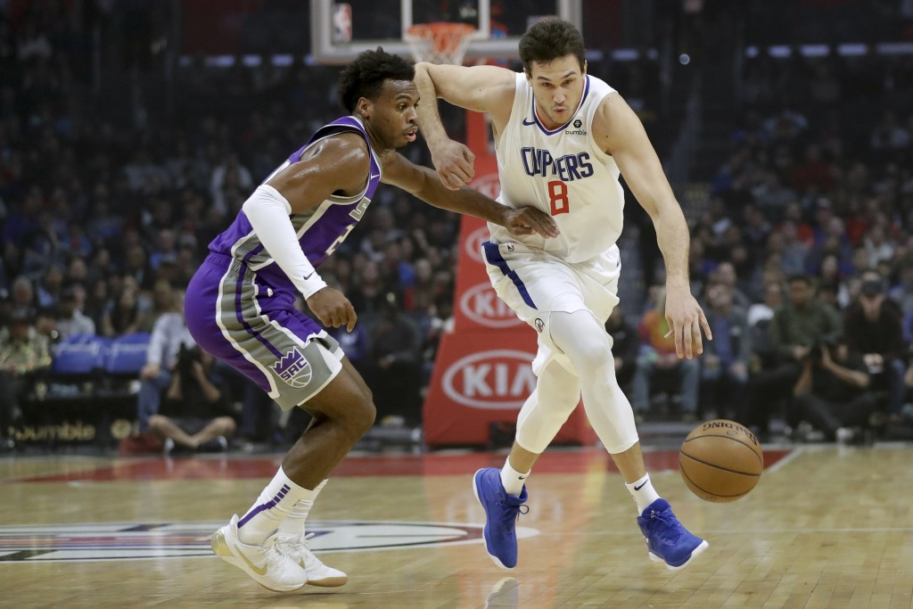 Los Angeles Clippers forward Danilo Gallinari, right, drives to the basket around Sacramento Kings guard Buddy Hield during the first half of an NBA b...