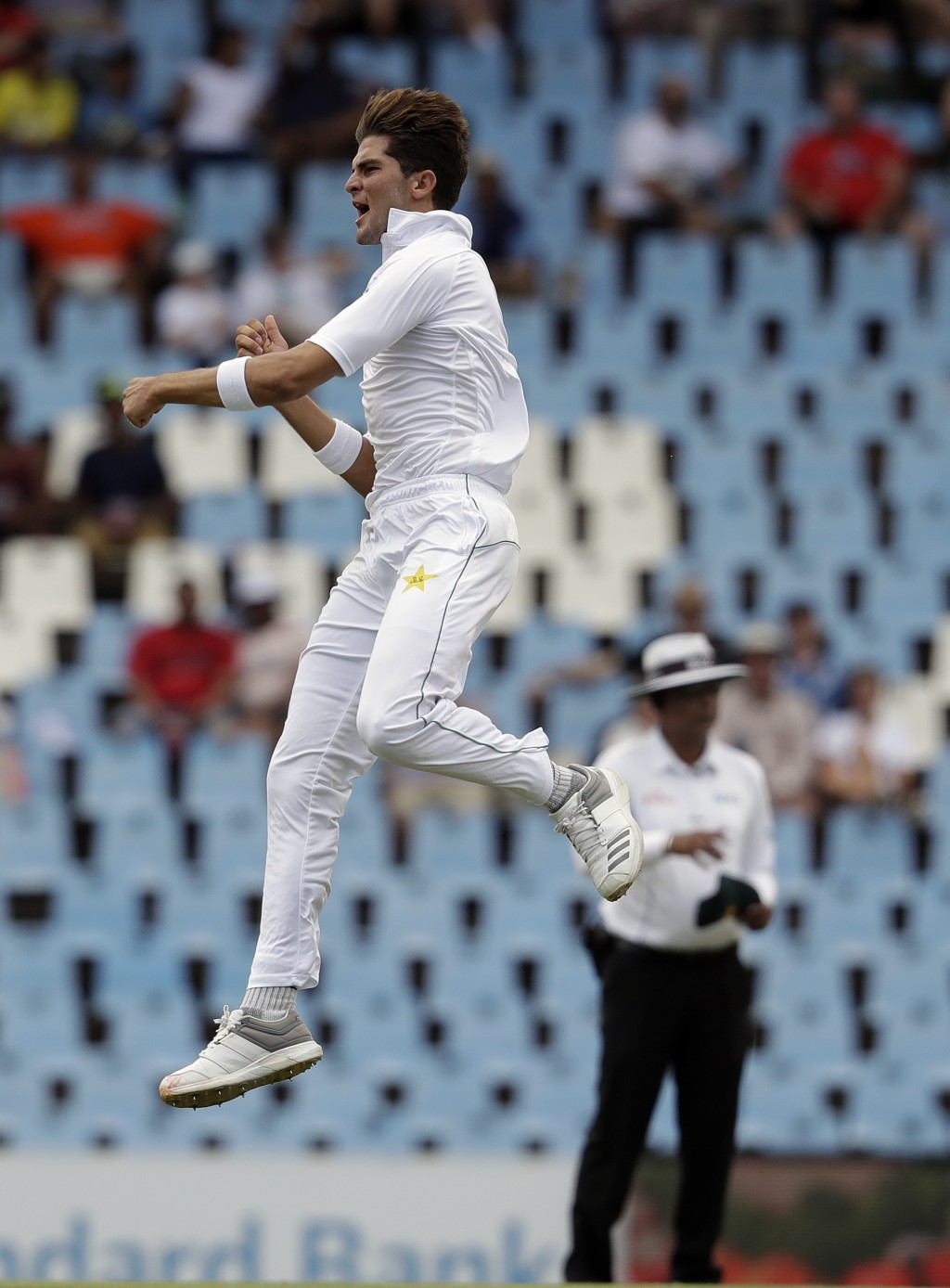 Pakistan's bowler Shaheen Afridi jumps as he celebrates after dismissing South Africa's batsman Temba Bavuma for 53 runs on day two of the first crick...