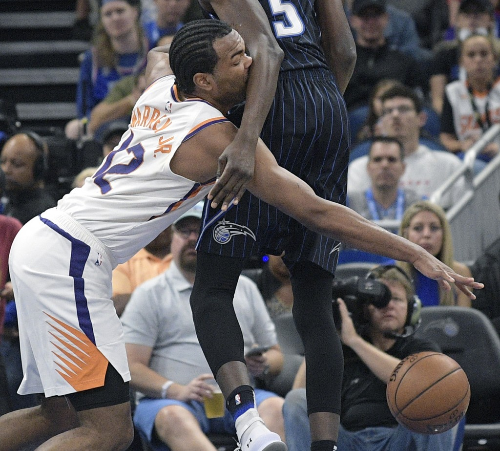 Phoenix Suns forward T.J. Warren (12) loses control of the ball after running into Orlando Magic center Mo Bamba (5) during the first half of an NBA b...