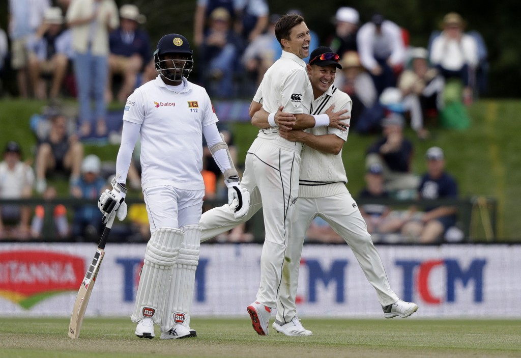 New Zealand's Trent Boult is congratulated by teammate Neil Wager, right, after taking the wicket of Sri Lanka's Lahiru Kumara during play on day two ...